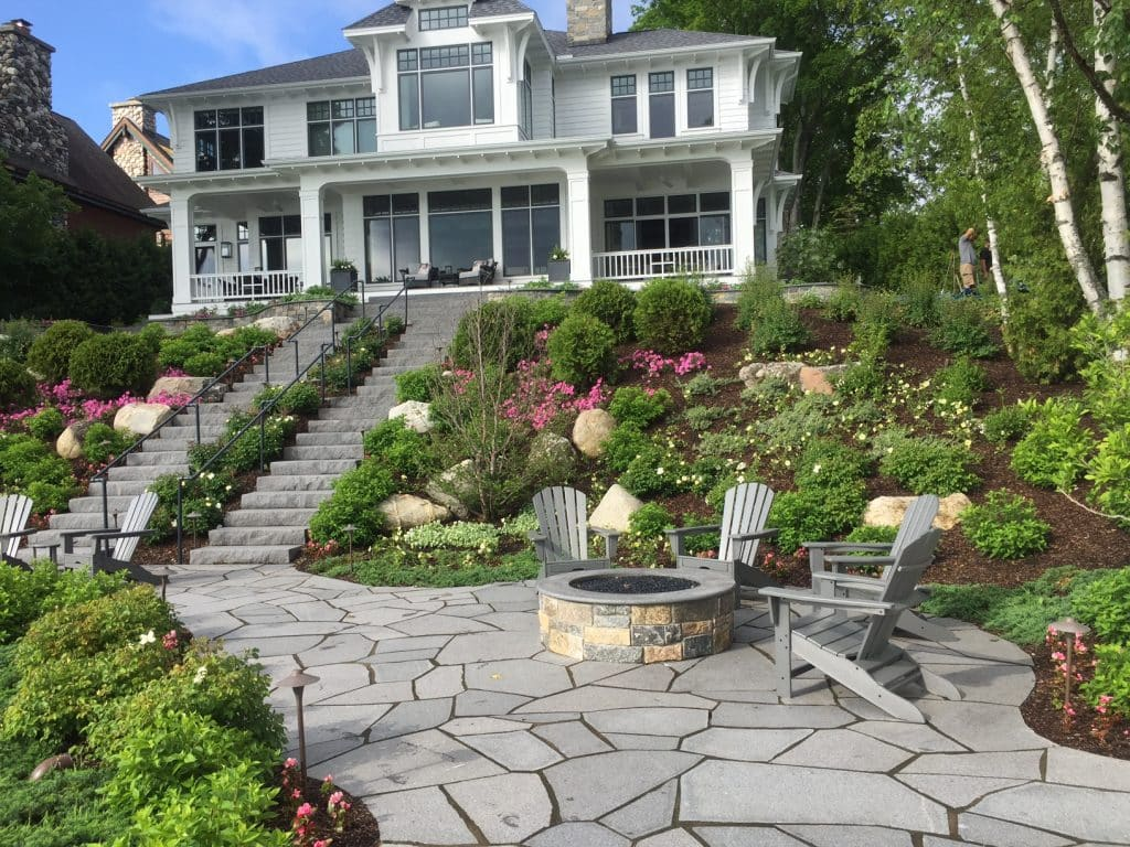 landscape installation including stone steps, stone walkway, stone patio, masonry fire pit and more