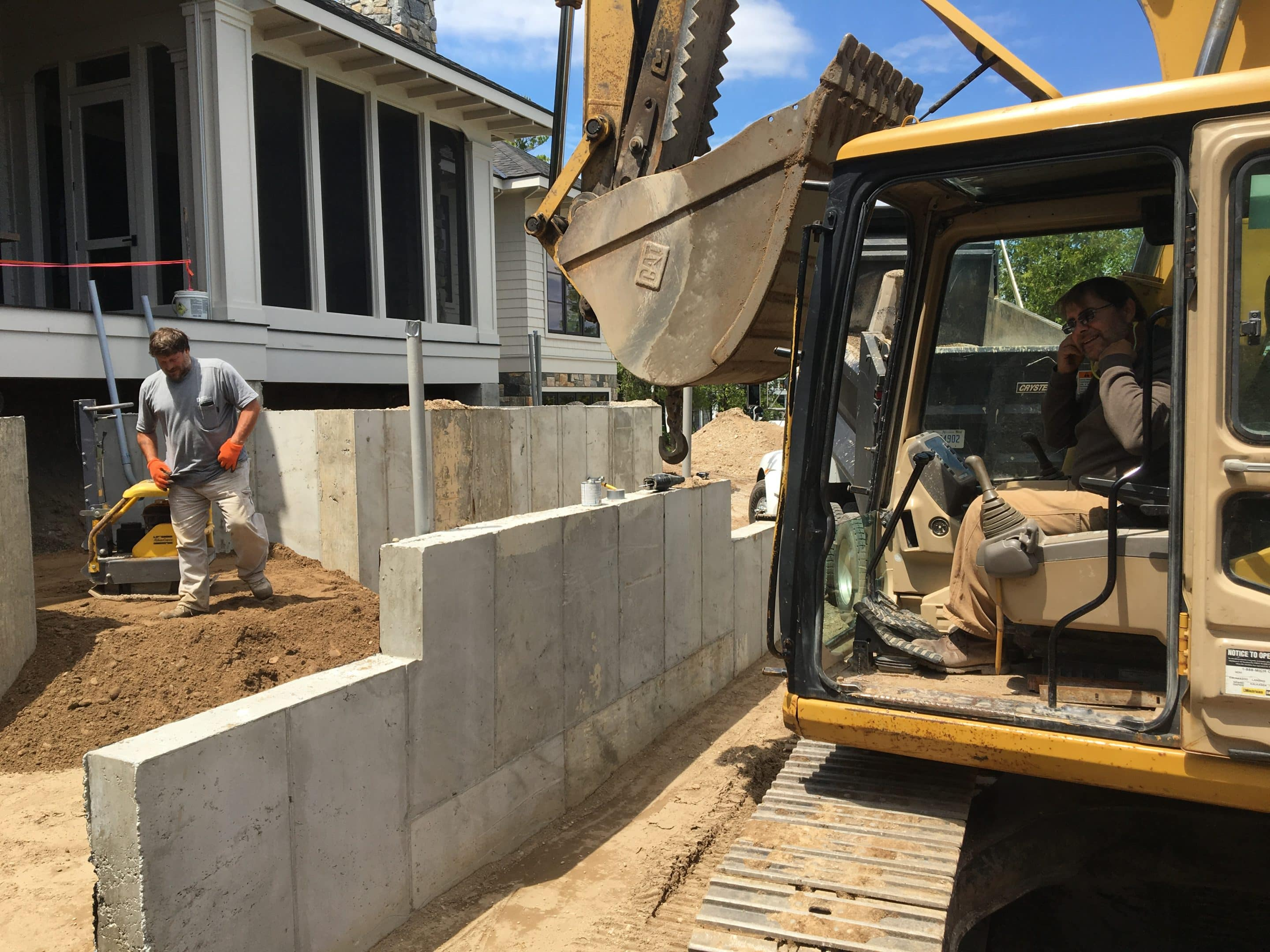 excavator by retaining wall