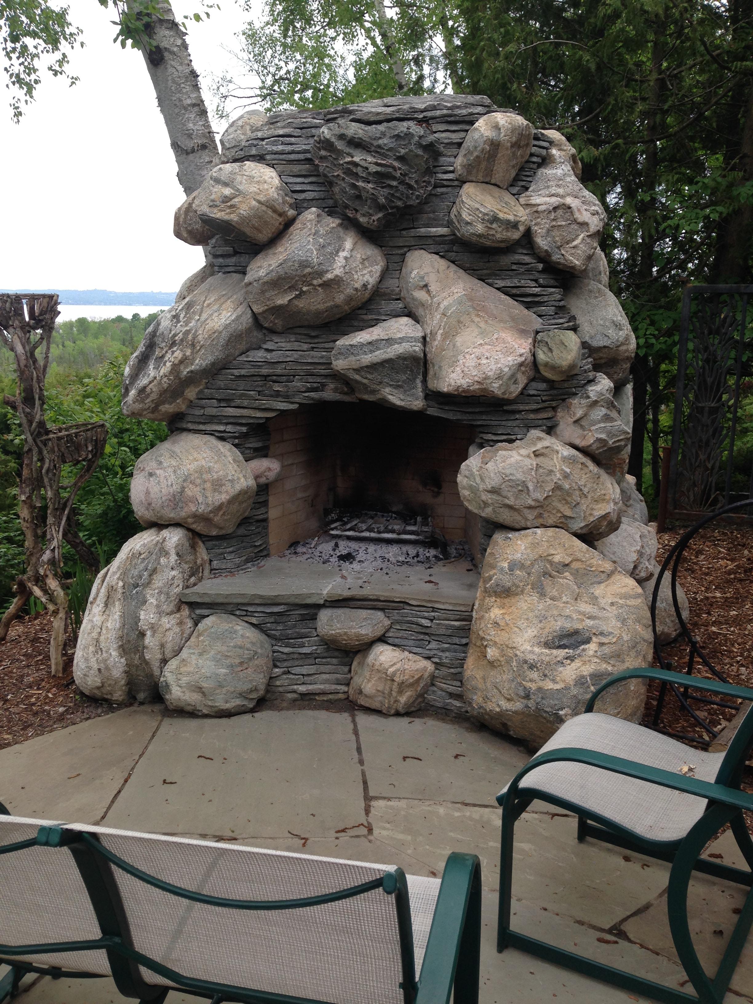 outdoor masonry fireplace using large stones