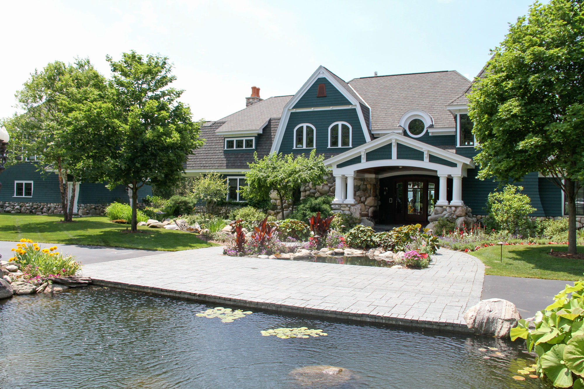 Pond water feature goes right up to driveway and walkway for a stunning first impression of visitors to this home