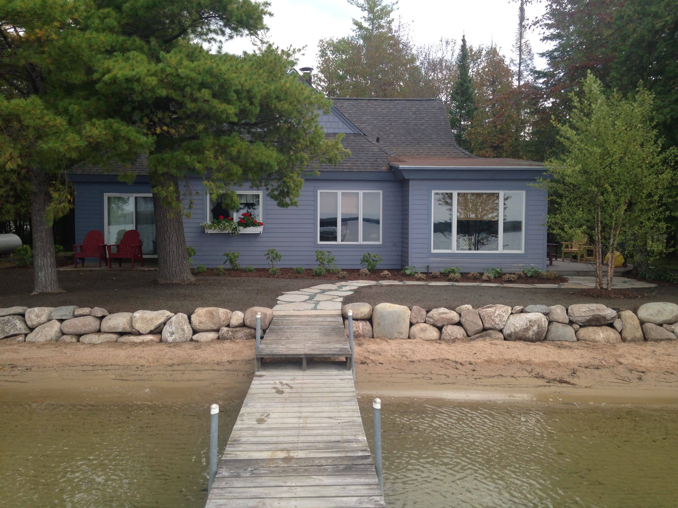 stone shoreline installation protects this property and stands out from the neighbors - viewed from a dock