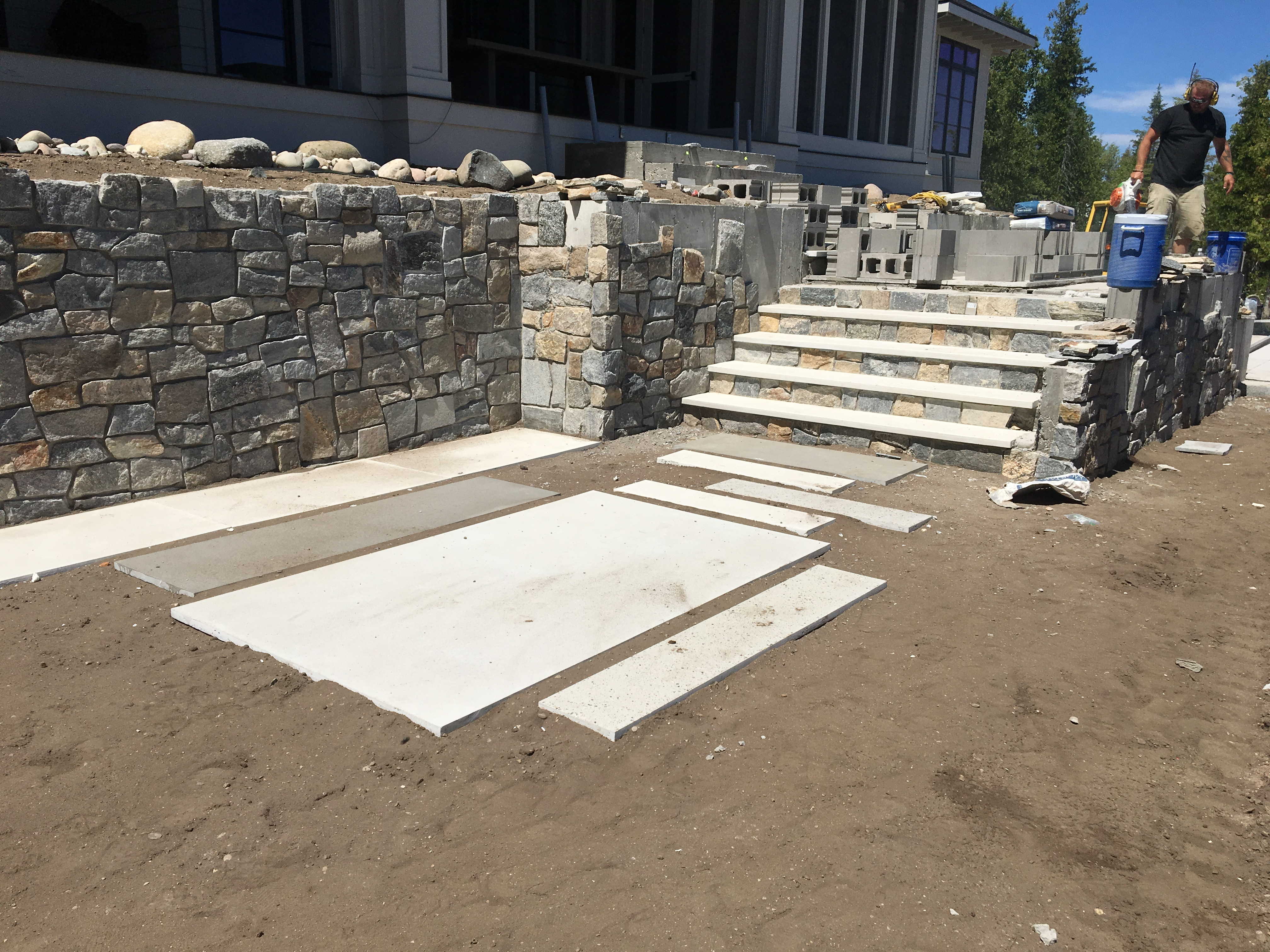 installation in process uses stone to beautifully hide concrete retaining wall